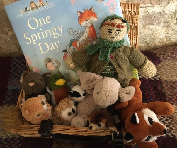 Wicker basket filled with soft toys and a book