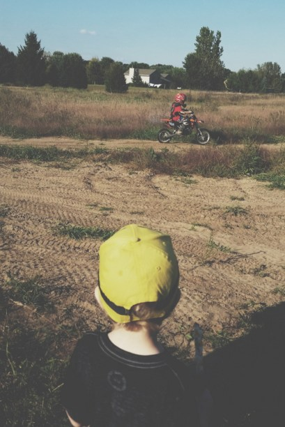Watching the boys dirt bike. He tried his hand at it earlier and has yet to become a fan of it.