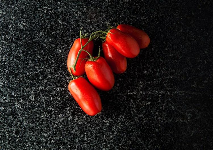 ripe tomatoes on black marble