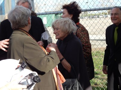 Margrit Mondavi, speaking to someone off-camera, with Jan and Maria Shrem in the background.