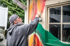 Brian Tschuor, Production Manager & Lighting Technician at The Vogue as well as accomplished artist, paints a mural on the front of the new Photographic Melodie outside event space. Photo cred Melodie Yvonne