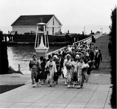 A group of immigrants walking on a causeway on Angel Island.