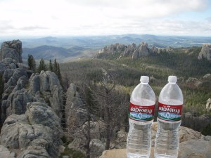 Two Arrowhead water bottles on a mountain peak, looking out across a park.