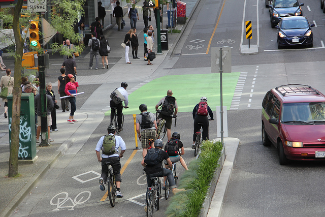 Cyclists wait in a dedicated bike lane, separated from car traffic by a barrier