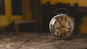 an alarm clock with a weathered, rusty face sits on a rustic wooden table
