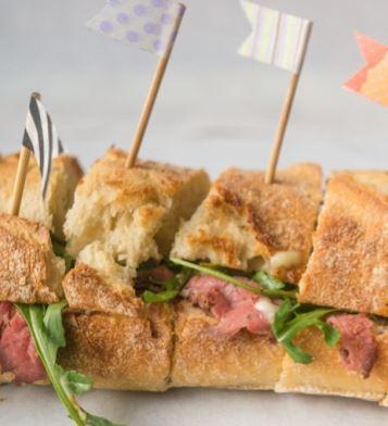 Gevuld stokbrood met Truffelmayonaise (jummie!) en rosbief. Beetje rucolade erbij en klaar. Stokbrood is in plakjes gesneden voor een feestje. leuk met vlaggetjes erin. Leuk en lekker gevuld stokbrood voor op de camping. Kampeer Recepten