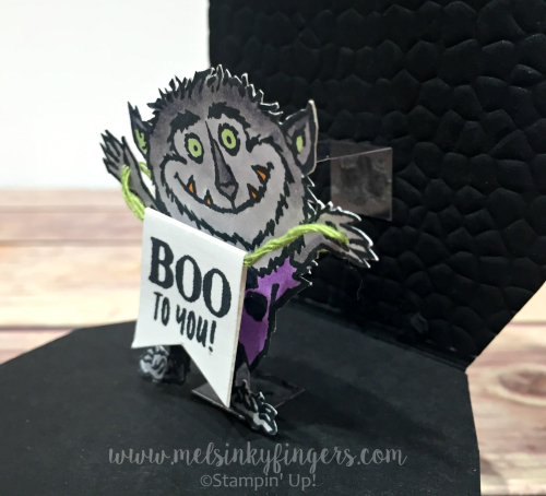 Attach your monster to the inside on a strip of window sheet to allow him to pop up.