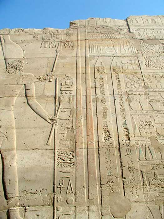 Depiction of Tuthmoses III at Karnak holding a Hedj Club and a Sekhem Scepter standing before two obelisks he had erected there.