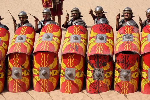 Roman Army reenactors in shielded formation, spears at the ready.