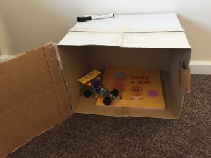 Picture of baby + me, a new sibling book, sitting in a box with other things treasured by the child.