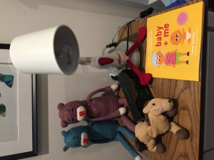 An image of baby + me, a new sibling book, sitting on a child's bedside table.