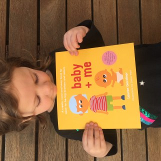 Picture of a child holding baby + me, a unique story book for soon to be big brothers and sisters.