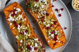 Vegetarian roasted butternut squash with pistachio pesto, grains, pine nuts, pomegranate and feta. A delicious fall recipe, perfect vegetarian Thanksgiving recipe.
