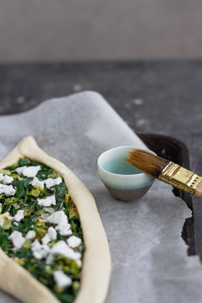 brushing pide dough with oil before baking