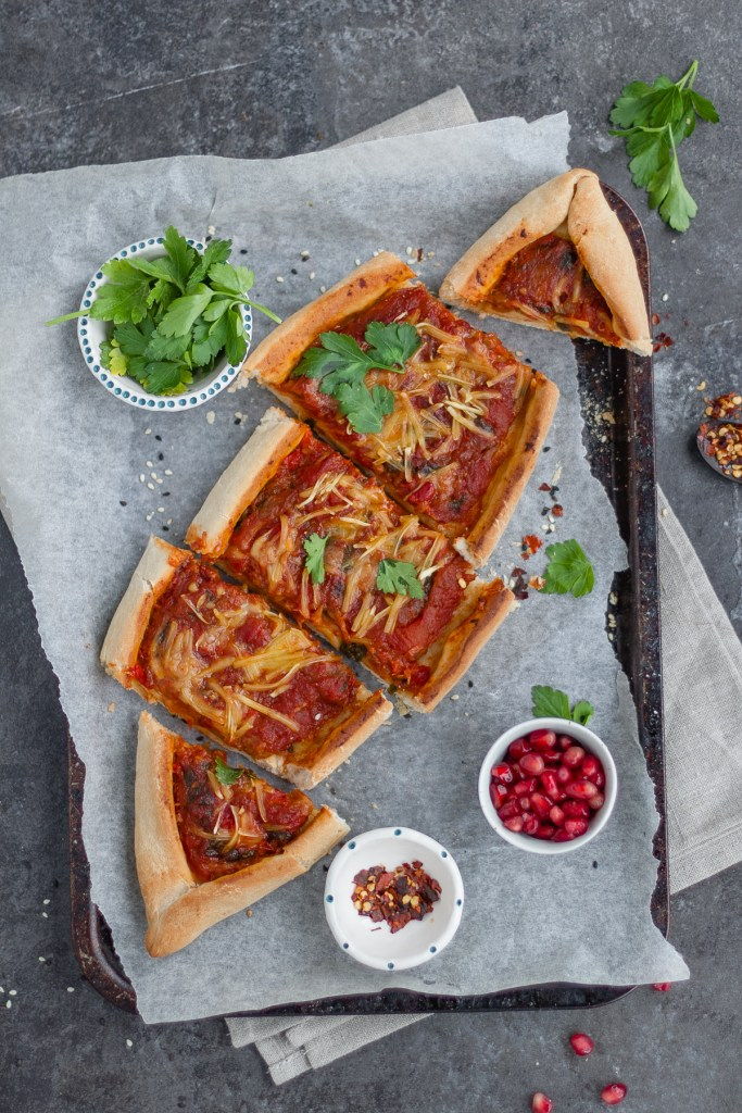 Spiced aubergine, tomato and red pepper vegan pide with pomegranate, parsley and chilli flakes