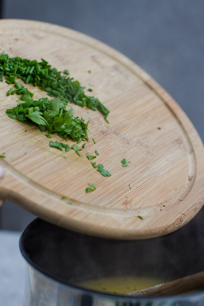 dropping chopped chives and parsley into polenta