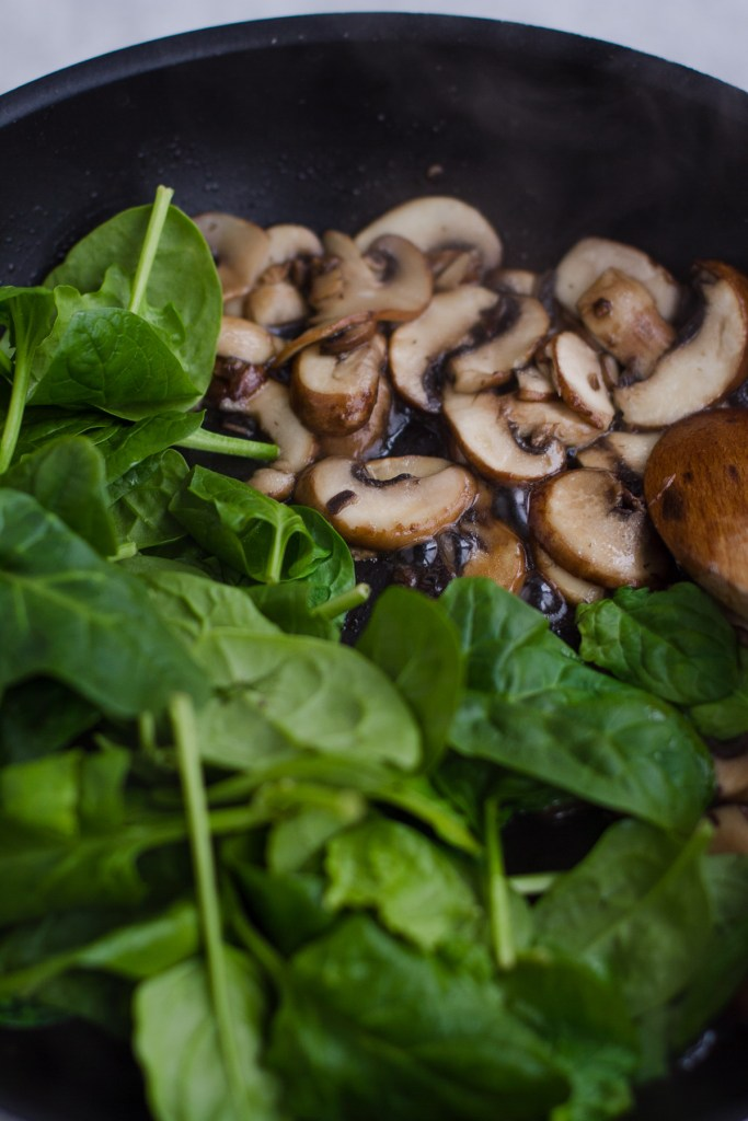 sauteed mushrooms and spinach in large frying pan