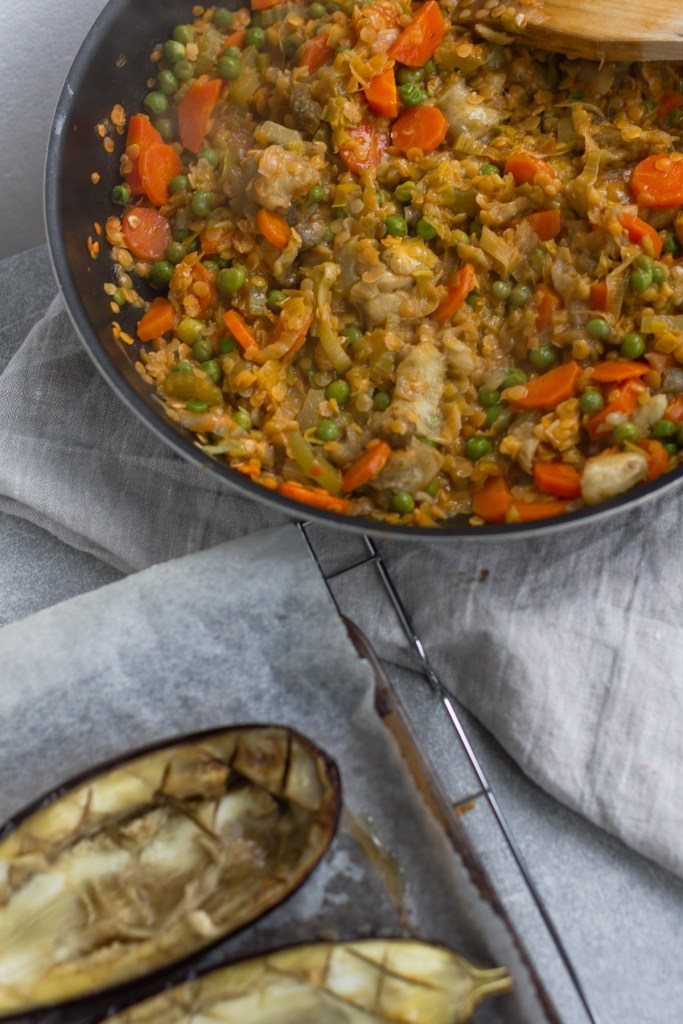 mixing baked aubergine into vegan lentil shepherds pie mix
