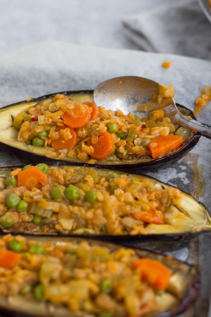 spooning lentil filling into baked aubergine