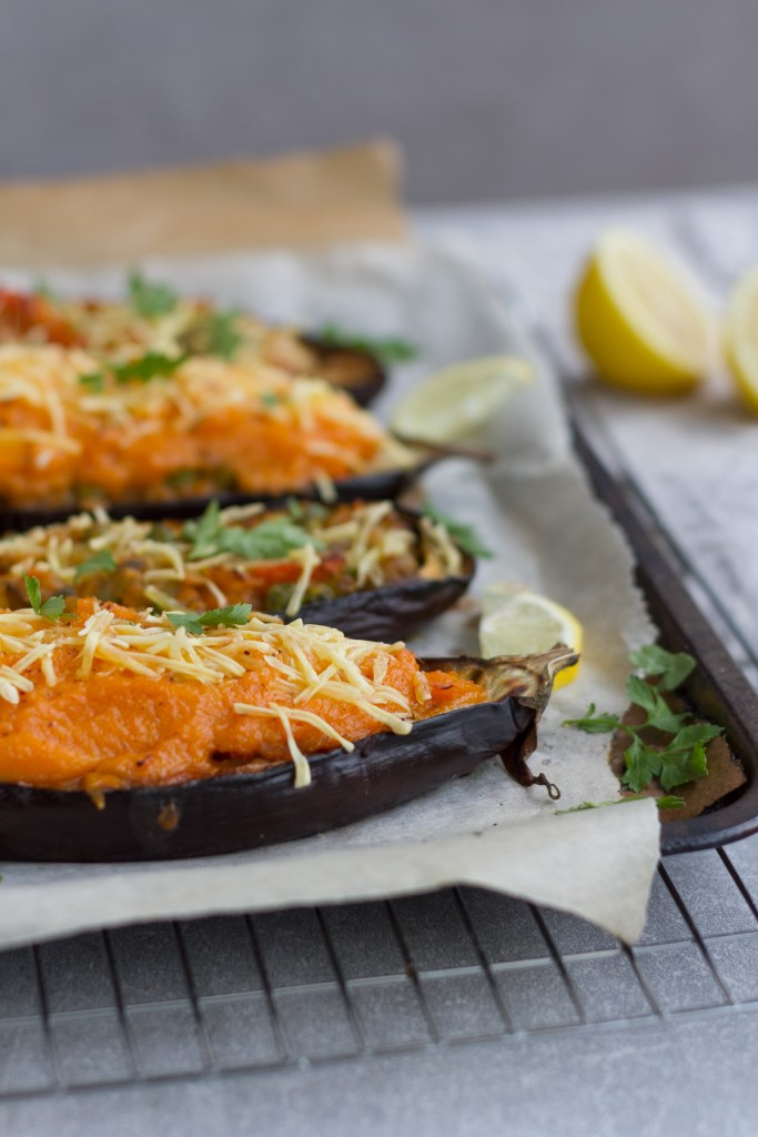 vegan shepherds pie stuffed eggplant topped with vegan cheese, parsley and lemon wedges.