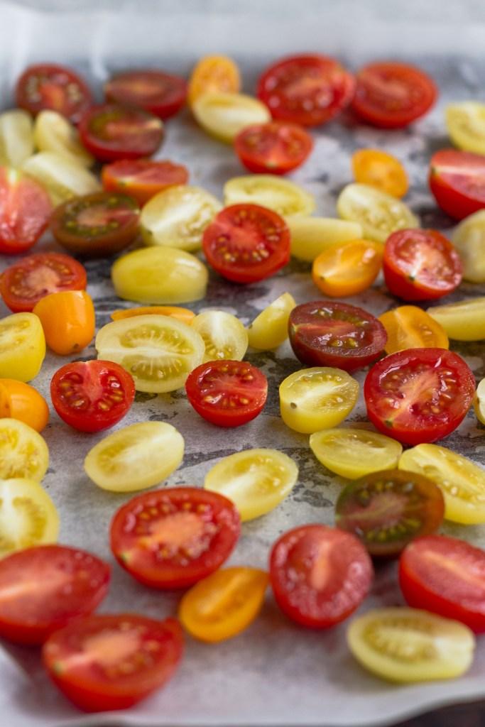 halved rainbow tomatoes on oven tray