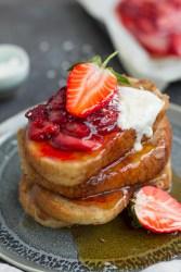 orange vegan french toast with maple glazed strawberries and coconut yogurt