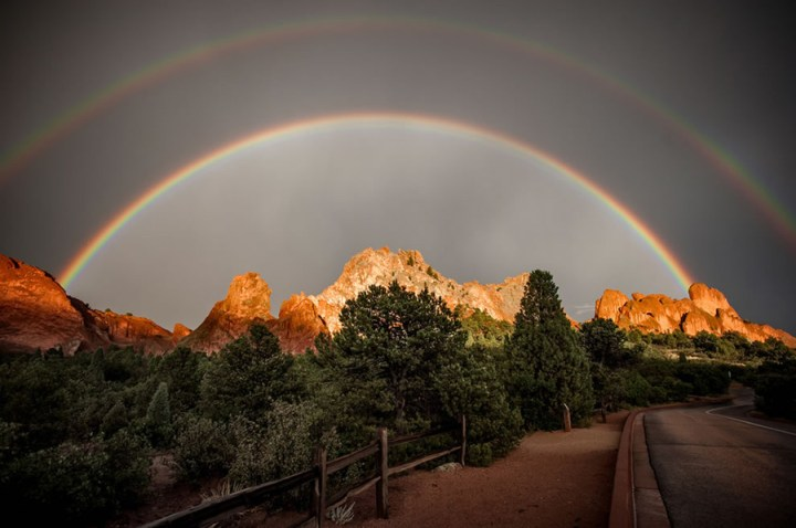 "Double rainbow over Garden of the Gods in Colorado Springs, CO. Did you know there really isn't an ""end"" to a rainbow? Maybe that's why finding a pot of gold is as hard as spotting a tricky leprechaun. If you stood at where I can see the ""proverbial"" end of the rainbow, then that rainbow would appear to you to be in a different spot. It's one of nature's very best optical ""illusion"" tricks. Experiencing the phenomenon depends upon where you are standing, where the sun is and where the moisture is just right in the air. Rainbows, especially double rainbows, are considered a positive, awe-inspiring sign in most cultures. Photo #1 by Raymond Larose"