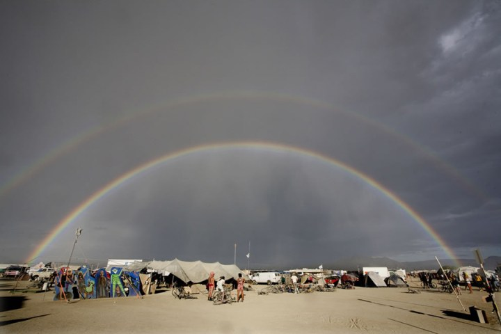 Double rainbow over Burning Man. You know about the pot of gold that Irish folklore says is at the end of a rainbow, but in Navajo and Hindu cultures, rainbows are interpretations of creation. In Australian Aborigines myths, the Rainbow Serpent is the god and the creator of all. Did you see The Avengers film? The Bifröst Rainbow Bridge connects Earth with Asgard, the home of the Norse mythology gods. The Greek messenger Iris was said to travel on a rainbow. Everybody and their dog has seen rainbows in all kinds of marketing. The real thing is pretty incredible to behold. Photo #8 by John curley