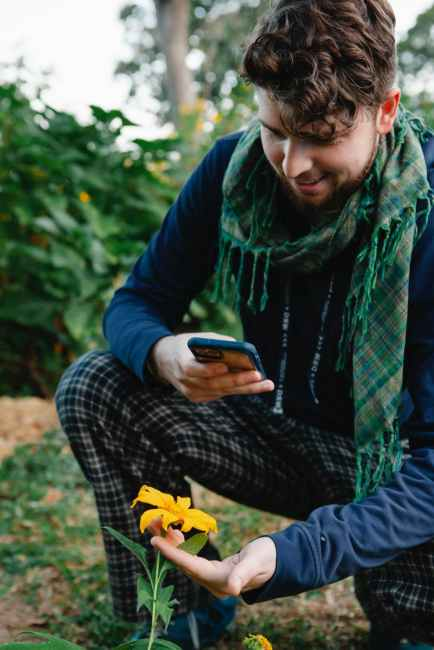 man in trendy outfit taking photo of flower with smartphone