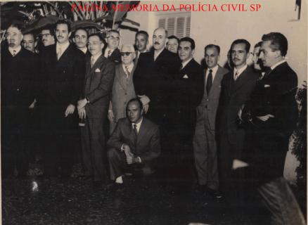 """Delegados de Polícia Coriolano Nogueira Cobra (ex DGP), perto da janela a esquerda e ao seu lado à direita calvo, alto de bigode Dr. Strasburgo; e Delegado Veras, terceiro da esquerda pra direita na frente, final década de 50. O Delegado Antônio Strasburg Machado de Moura, foi quem esclareceu o caso do """"Chico Picadinho"""", na rua Aurora, em agosto de 1.966. O quinto da esquerda para direita (gravata escura) é o Dr. José René Motta (ex DGP). (acervo pessoal da Sra. Teresa Cobra)."""