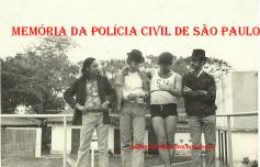 """Da direita para a esquerda; o repórter policial Percival de Souza, em início de carreira; o ex- Detetive do Estado da Guanabara, Mariel Mariscot de Matos; o ex- Guarda Civil optante Investigador Adhemar Augusto Pereira """"Fininho 1"""", ambos já falecidos, e (?), quando os dois policiais encontravam-se refugiados no Paraguai e aceitaram serem entrevistados, em 1.972. Curiosidade da foto é o Mariel com a camiseta de Salva Vidas, sua antiga profissão, brincando com o Fininho 1, introduzendo o dedo no cano de sua arma."""