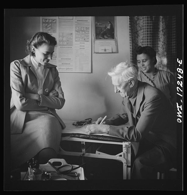 Penasco, New Mexico. Doctor Onstine, medical doctor, writing a prescription in the clinic operated by the Taos County cooperative health association.  1943 Jan.  John Collier, photographer  (Library of Congress)