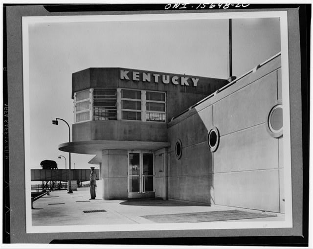 Kentucky Dam, close to the mouth of the Tennessee River, will be one of the biggest projects of the Authority and will back the water up for a distance of 185 miles. It will be completed in 1944. This photograph shows a partial view of the lock operation building, with the commanding officers work space, shaped somewhat like a control cabin in the foreground on the second floor. The near wing contains visitors rest rooms while the lock switchboard is in the far wing, entered through the door in the foreground of the picture. Visitors are admitted to the various roof levels to watch the locking operation (between 1933 and 1945)