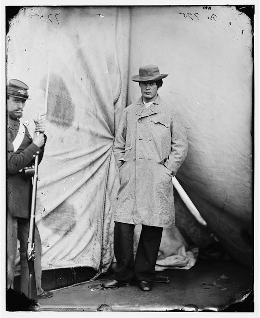 Washington Navy Yard, D.C. Lewis Payne (Powell), the conspirator who attacked Secretary Seward, standing in overcoat and hat.  April 1865.  Alexander Gardner, photographer.