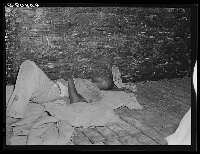 African-American male asleep on slatted floor of an empty boxcar.
