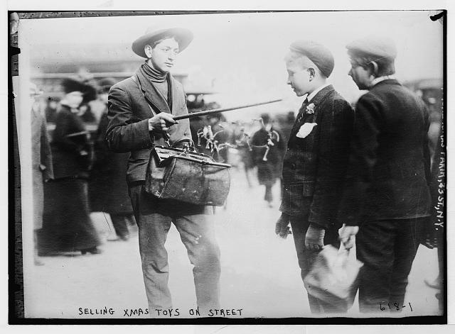Street vendor showing Christmas toys to boys 23rd., St. New York.  December 7, 1908