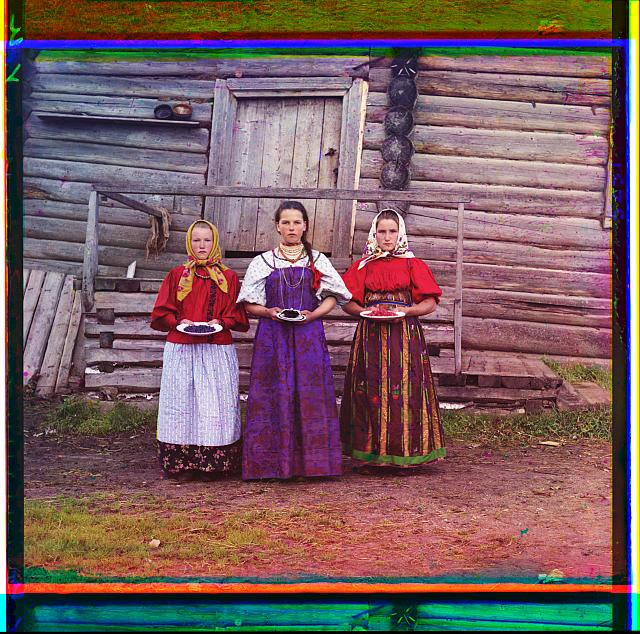 Three young peasant women offer berries to visitors to their izba, a traditional wooden house, in a rural area along the Sheksna River, near the town of Kirillov, Russian Empire.  c1909.  Forms part of: Sergei Mikhailovich Prokudin-Gorskii Collection (Library of Congress)