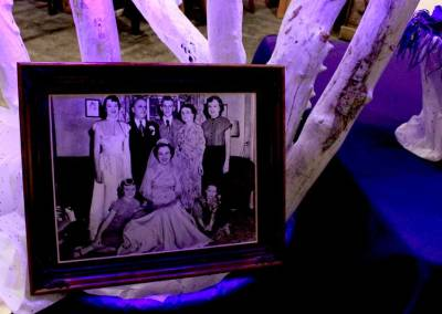 A photo of the family of artist Paul Coté is displayed next to a piece of his driftwood art sculpture. Coté's father and five aunts, all pictured here, died of Alzheimer's disease.
