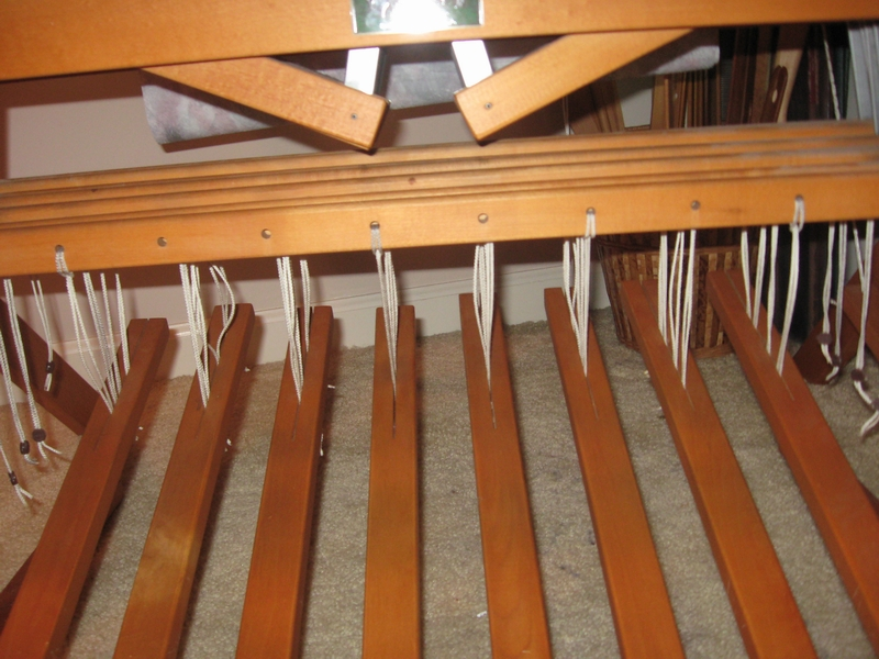 Foot treadles are tied up to the correct sequence of harnesses which hold the heddles.  There are 8 harnesses and 10 treadles on this loom.
