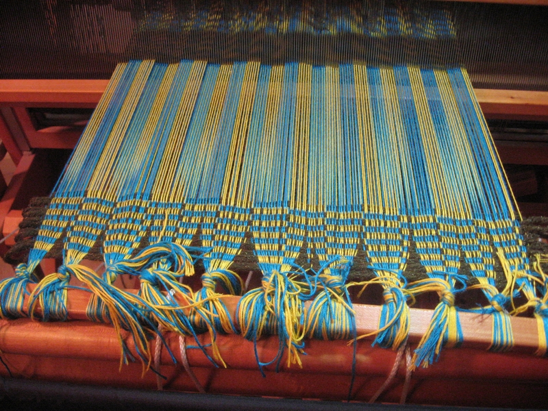 """A header of """"junk yarn"""" is woven to even out the warp threads and prepare for weaving."""