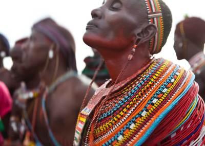 Marcy Mendelson, The Samburu Story | A Samburu mother dances alongside hundreds of moran, celebrating their graduation into elder warrior status of the Loimisi Samburu clan.  Outside Kisima village, Samburu, Kenya.