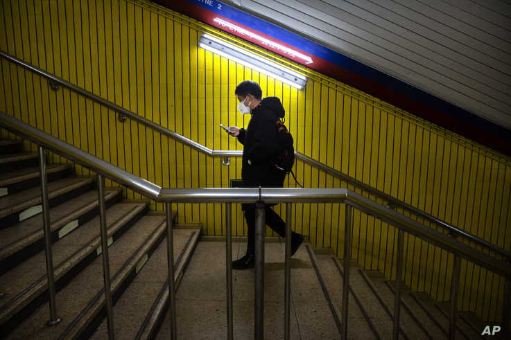 A man wearing a face mask walks through a normally busy subway station during the morning rush hour in Beijing, Monday, Feb. 3,…