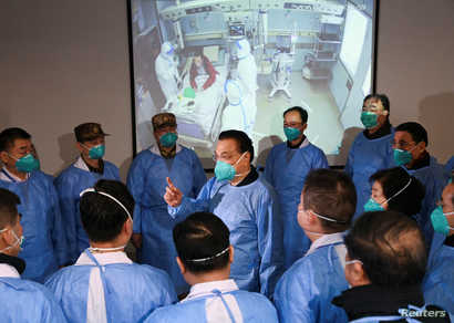 Chinese Premier Li Keqiang wearing a mask and protective suit speaks to medical workers as he visits the Jinyintan hospital…