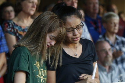 FILE - High School students Celeste Lujan, left, and Yasmin Natera mourn their friend Leila Hernandez, one of the victims of the Saturday shooting in Odessa, at a memorial service in Odessa, Texas, Sept. 1, 2019.