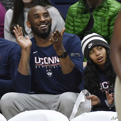 Kobe Bryant and his daughter Gianna watch the first half of an NCAA college basketball game between Connecticut and Houston,…