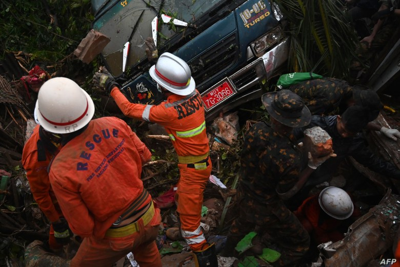 Rescue workers attempt to free a cow caught under a van after a landslide in Paung township, Mon state, Aug. 10, 2019.