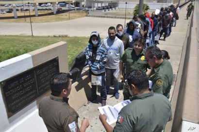 U.S. Border Patrol officers return a group of migrants back to the Mexico side of the border, as Mexican immigration officials check a list, in Nuevo Laredo, Mexico, July 25, 2019.
