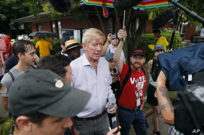 FILE - Republican presidential candidate and former Massachusetts Gov. Bill Weld, center, walks to the grand concourse during a visit to the Iowa State Fair, in Des Moines, Iowa, Aug. 11, 2019.