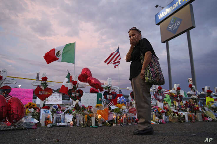 Catalina Saenz wipes tears from her face as she visits a makeshift memorial near the scene of a mass shooting at a shopping…