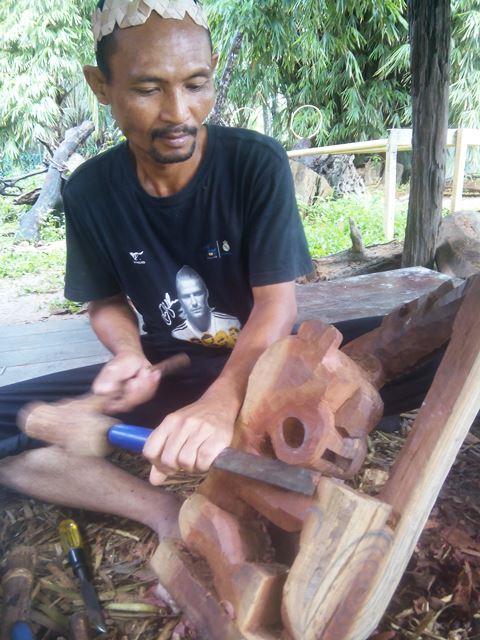 Seorang pria Suku Mah Mire sedang membuat ukiran dari kayu Nire Batu. Foto by menixnews.com